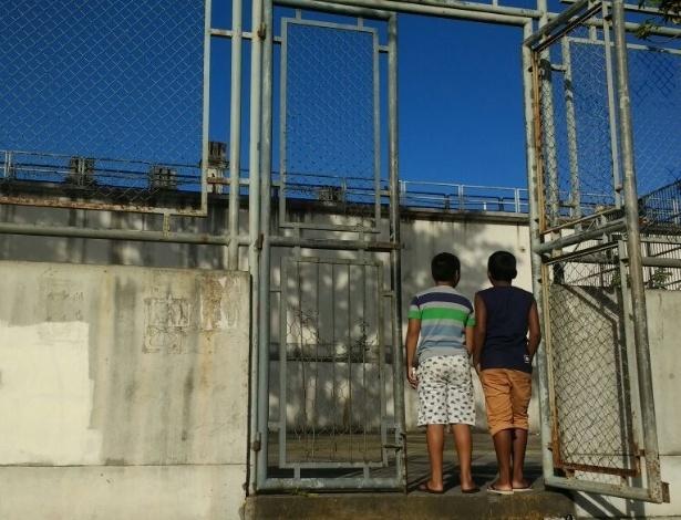 Garotos observam muro da cadeia a partir da quadra onde não podem mais jogar futebol